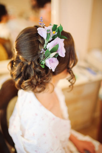 Bride Wearing Flowers On Hair While Sitting On Chair