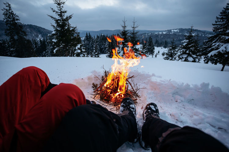 Fire - Natural Phenomenon Snow Cold Temperature Fire Winter Flame Burning Nature Low Section Real People Human Body Part One Person Land Leisure Activity Tree Bonfire Body Part Human Leg Outdoors Campfire Camping Winter Weekend Activities Nature Forest