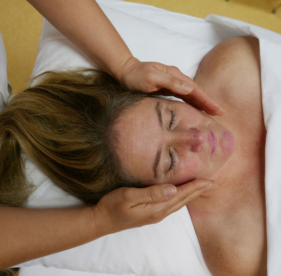 High angle view of woman having reiki treatment at spa