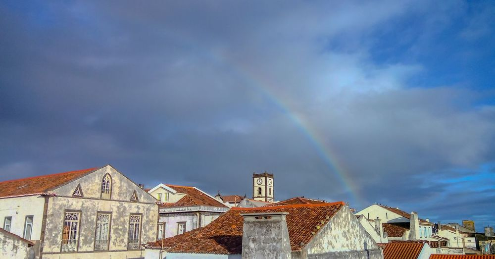 Low angle view of rainbow over buildings in city