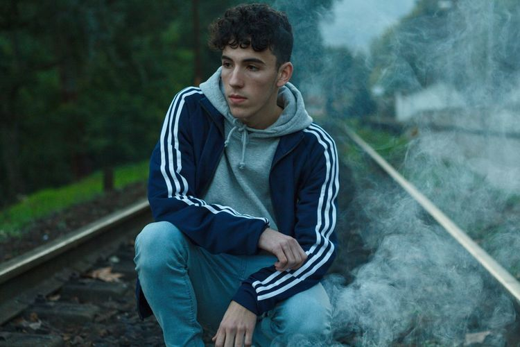 Thoughtful Teenage Boy Crouching On Railroad Track
