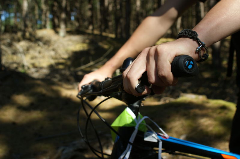 Cropped hands of person holding bicycle handlebar in forest