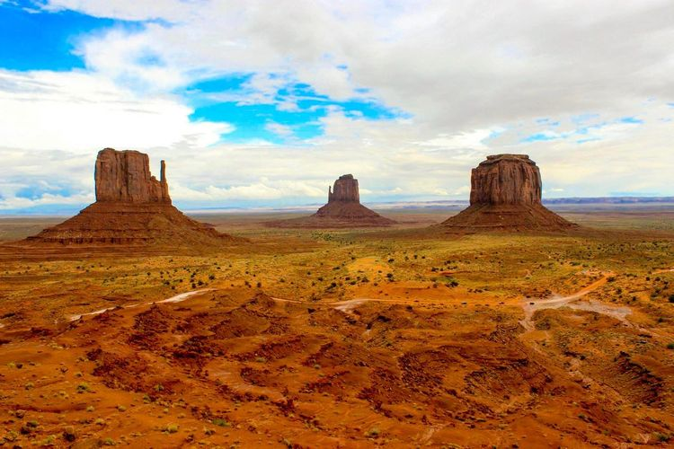 Scenic View Of The Mittens At Monument Valley Against Cloudy Sky