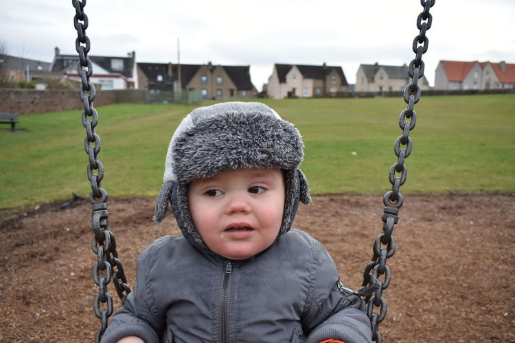 Close-Up Of Cute Boy Wearing Fur Hat Playing On Swing In Playground