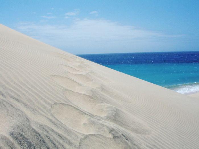 Sand dune at beach against sky at fuerteventura
