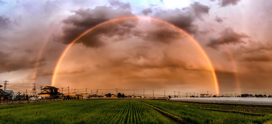 Scenic view of rainbow over field during sunset