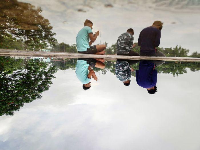 People looking at lake against sky