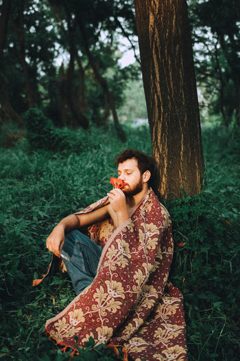 Young man with blanket smelling flower while sitting at forest