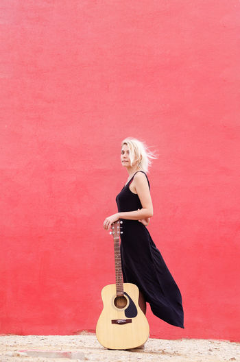 Vertical photo of a young beautiful blond woman in a black dress standing leaning on a guitar