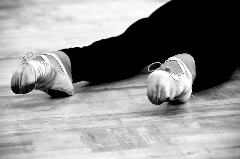 Low section of ballerina lying on floor