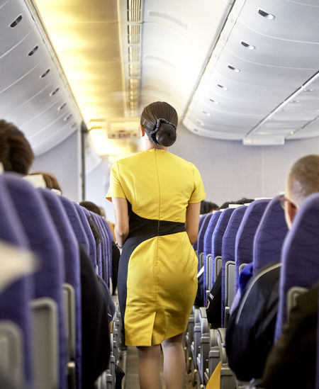 Rear View Of Airhostess In Airplane