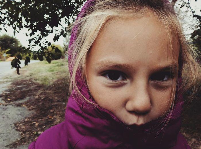 Portrait of cute girl hiding in park