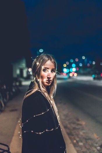 Side View Portrait Of Young Woman With Illuminated String Lights Standing On Street At Night