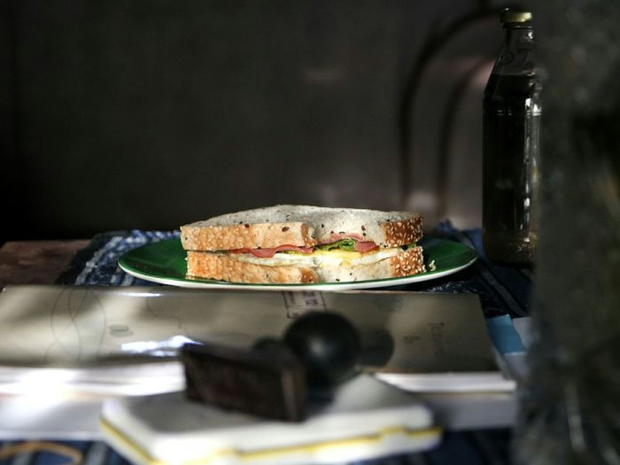 High angle view of sandwich in plate by book on table