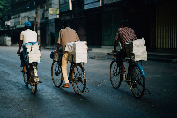 Rear View Of Newspaper Vendors Riding Bicycles On Road In City