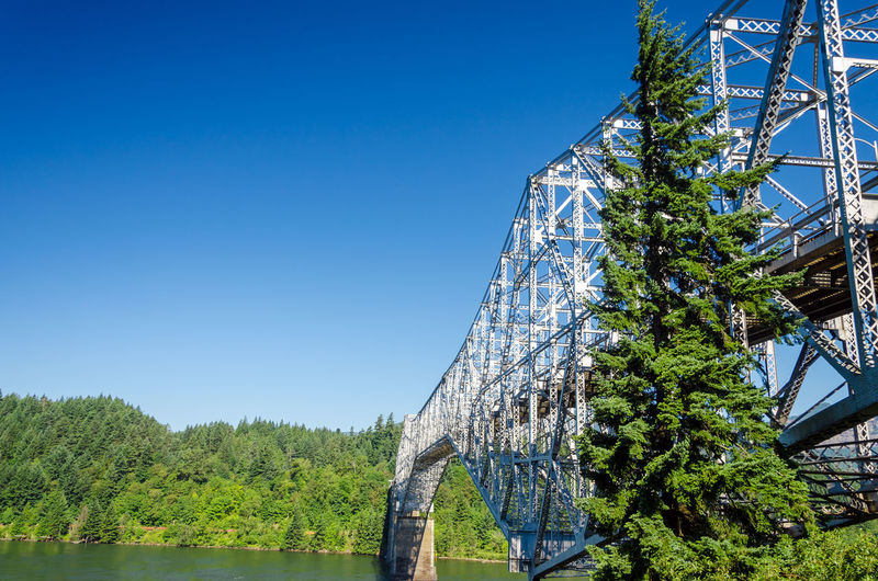 Low angle view of bridge of the gods over columbia river gorge against clear blue sky
