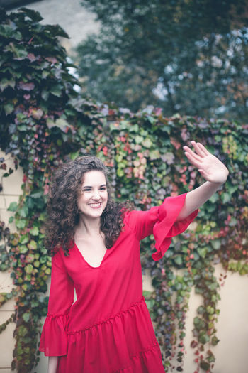Smiling young woman in red dress walking outdoors, waving her hand. curly hair brunette, autumn