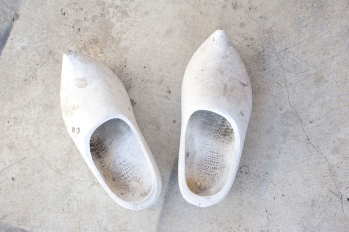 a pair of old wooden clogs Clogs Concept Concrete Dirty Dutch Grunge Holland Neatherlands Old Out Of Date Plain Poor  Shoes Simple Undecorated Wooden