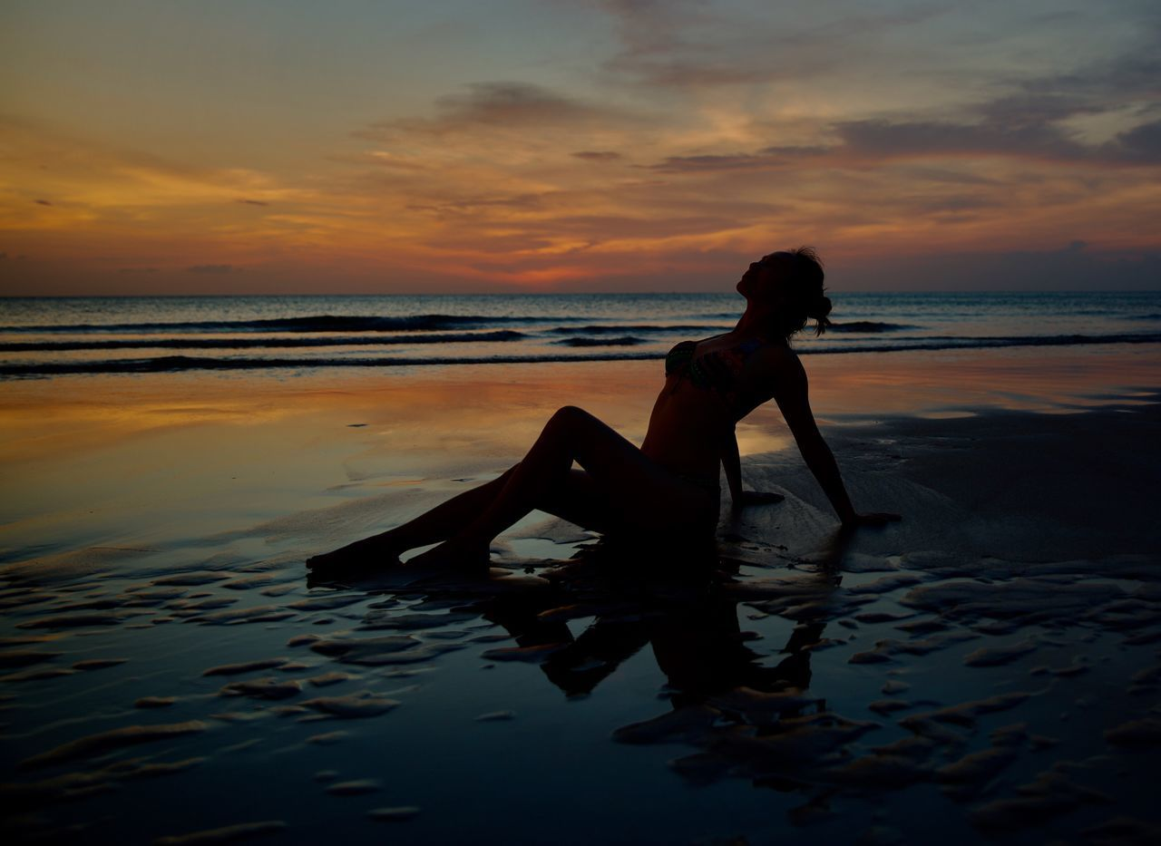 Silhouette Woman Relaxing On Shore At Beach During Sunset