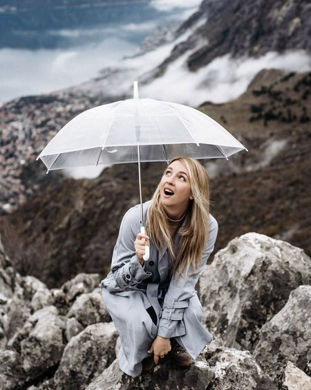 Portrait of a young woman standing on rock with umbrella