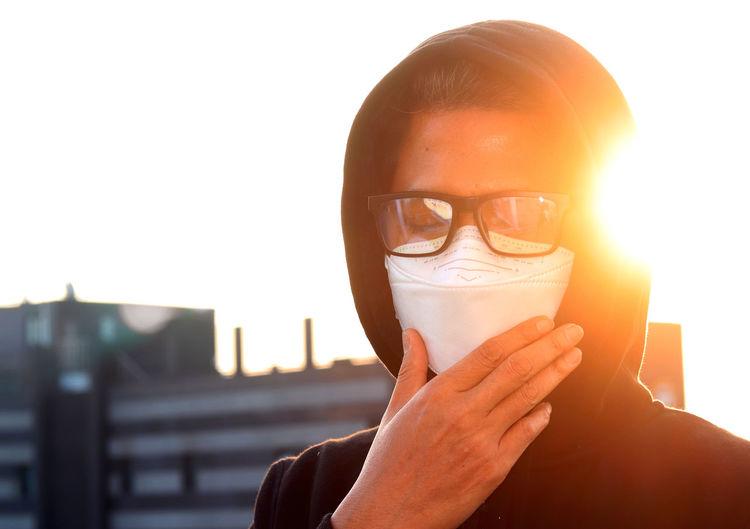 Close-up of man wearing flu mask standing outdoors