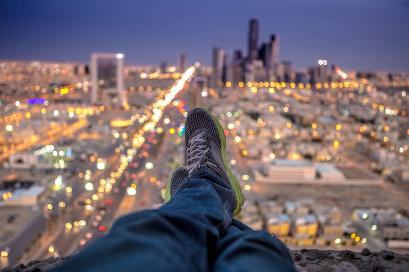 Low section of man sitting on cliff against illuminated cityscape