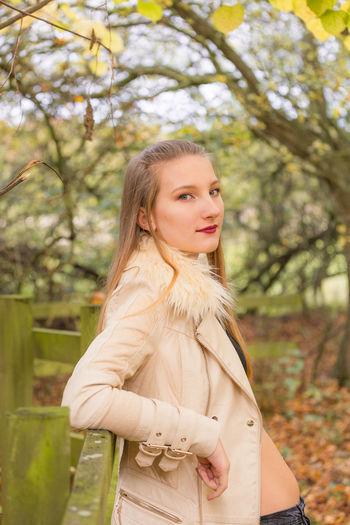 Portrait of girl leaning on railing against trees