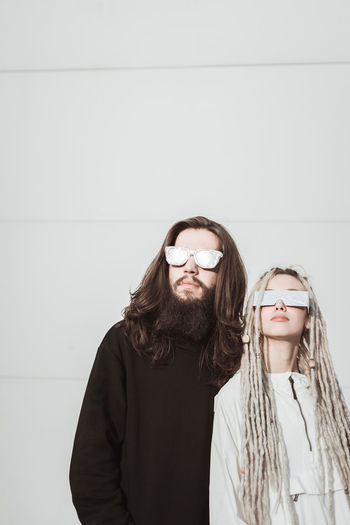 Futuristic young couple with metallic shades against white wall Glasses Eyeglasses  Young Adult Front View Wall - Building Feature Facial Hair Young Women Adult Two People Standing Copy Space Beard Lifestyles Waist Up Casual Clothing People Portrait Young Men Indoors  Couple - Relationship Hairstyle Warm Clothing
