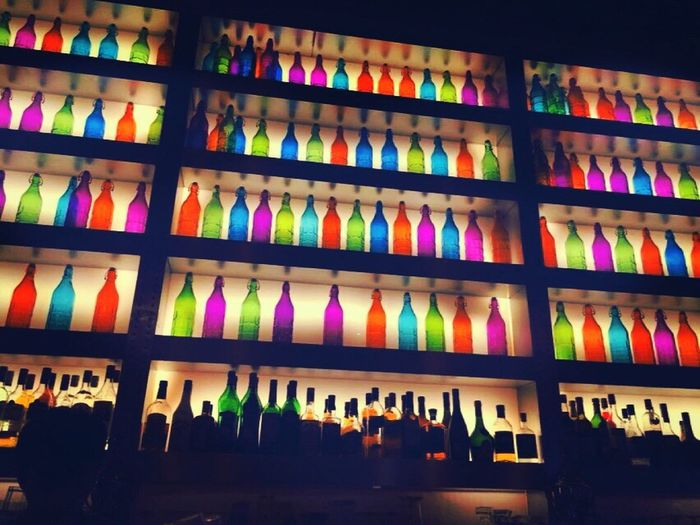The Color Of Business Multi Colored Colorful In A Row Arrangement Variation Illuminated Order Abundance Night Large Group Of Objects Shelf Collection No People Vibrant Color Retail  Arranged Colors Little Pub English Pub Rebel Rebel Bottle Wall Bottle Art