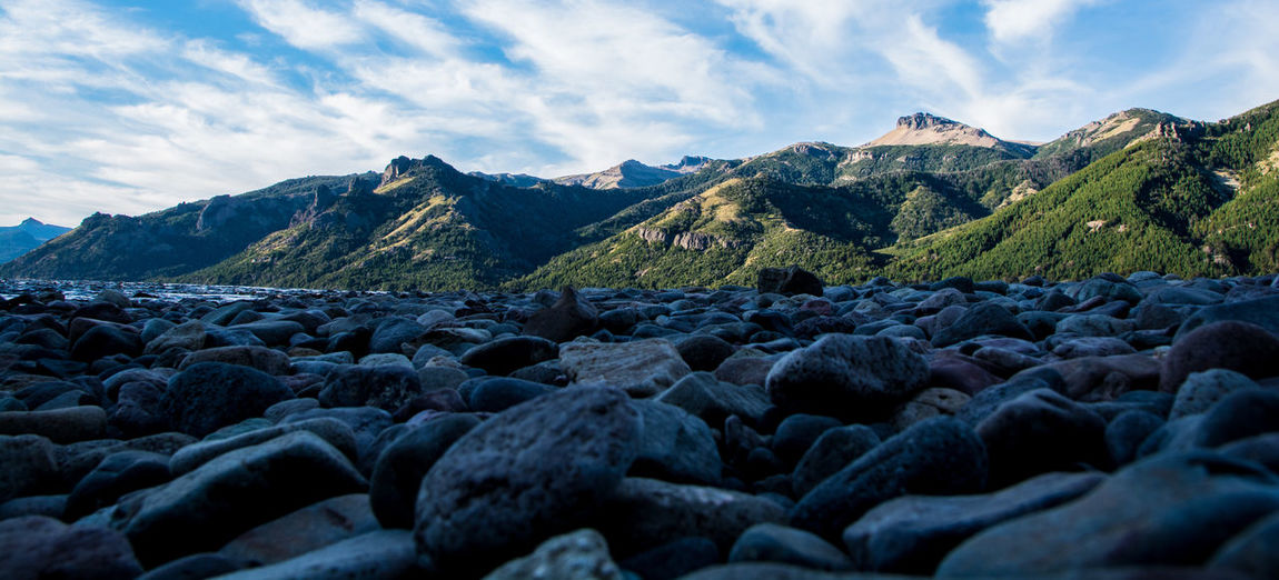 Scenic view of pebbles and mountains against sky