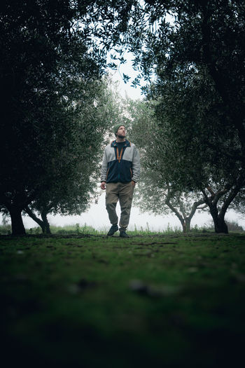 Man standing on field against trees