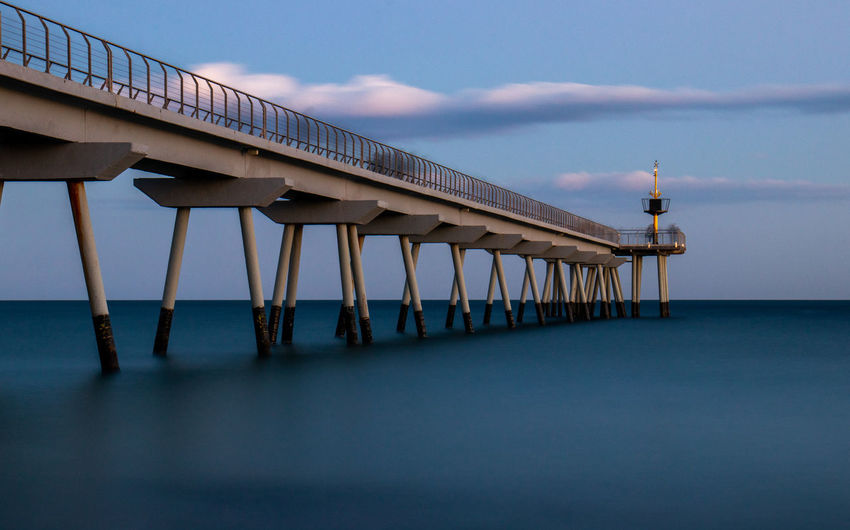 Sky Architecture Water Built Structure Sea Cloud - Sky No People Horizon Over Water Nature Pier Horizon Scenics - Nature Outdoors Day Building Exterior Blue Beach Beauty In Nature Travel Destinations Architectural Column Pont Del Petroli Pont Del Petroli, Badalona, Spain Long Exposure Clouds Calm Place