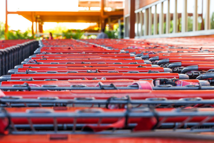 Selective focus on row of shopping carts at supermarket entrance Economy Entrance Shopping Supermarket Trolley Arrangement Cart Consumerism Convenience Store Custom Empty Food Groceries In A Row Metal Money Order Outdoors Purchase Red Repetition Row Selective Focus Urban