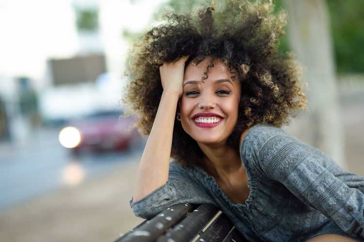 Portrait Of Smiling Young Woman Sitting On Bench In City