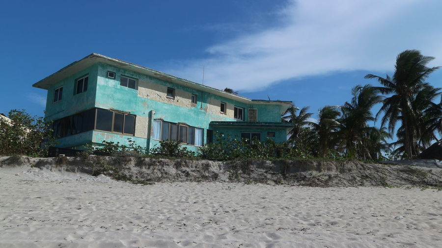 Abandoned building by beach against sky