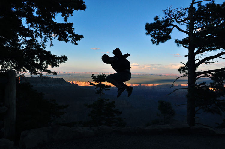 Springender Mann am Grand Canyon, Arizona, USA Abenteurer Abgrund Amerika Arizona Bäume Colorado Plateau Dämmerung Felsen Grand Canyon Guy Hüpfen Landschaft Mann National Park Nature Nordamerika Schatten Silhouette Sonnenuntergang Sportler Springen Sprung USA Vereinigte Staaten Wanderer
