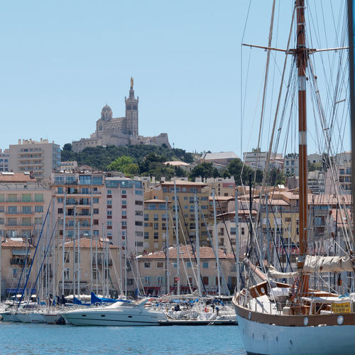 Notre Dame De La Garde Marseille Church Harbor Summer Summertime France Water Cityscape Blue Sky Outdoors Nautical Vessel Transportation Mode Of Transportation Sailboat Sky Pole Architecture Sea Mast Clear Sky Building Exterior Nature Built Structure Moored Sailing Day No People Port Marine Marina Yacht