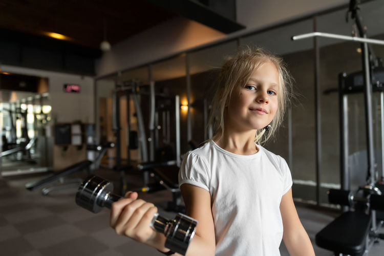 Portrait of smiling girl exercising at gym