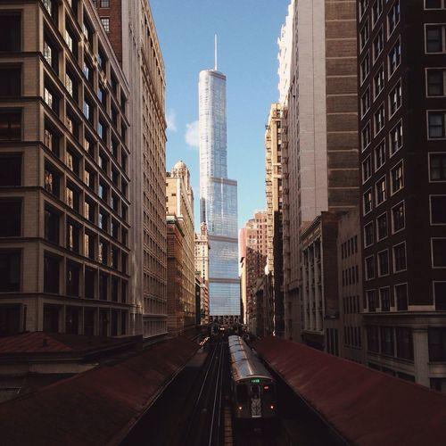 Train amidst modern city against sky