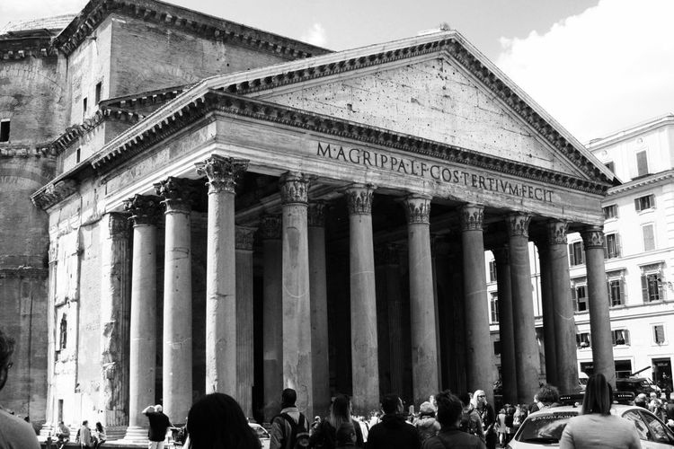 People walking in front of pantheon in city