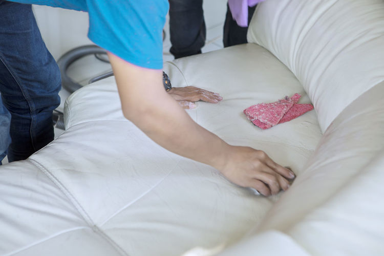 Midsection of person cleaning sofa in living room at home