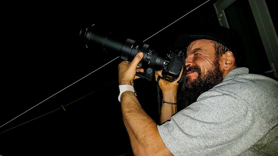 Side view of man photographing at night