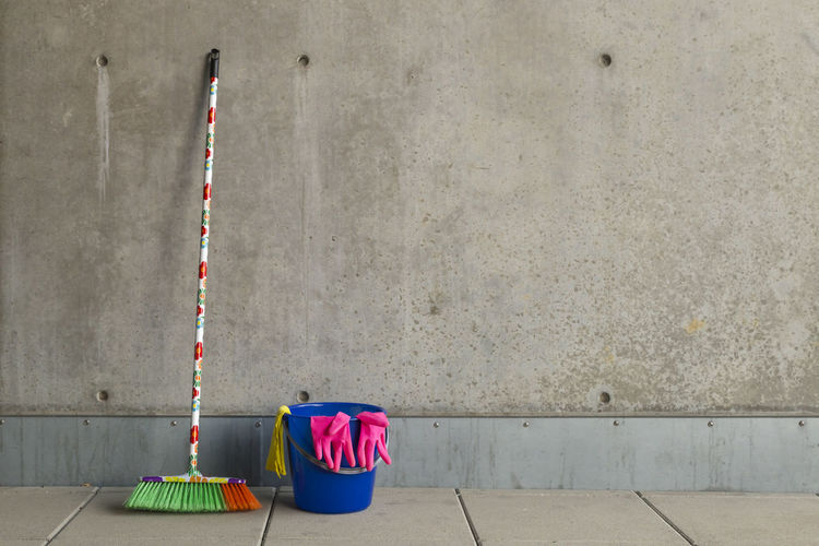 Multi Colored Broom With Bucket On Floor Against Wall