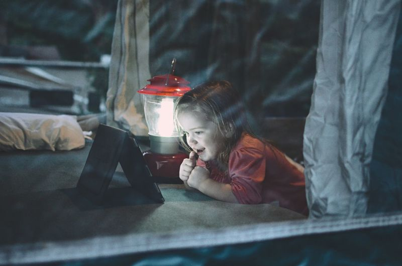 Girl Looking At Digital Tablet By Illuminated Lantern On Bed At Home