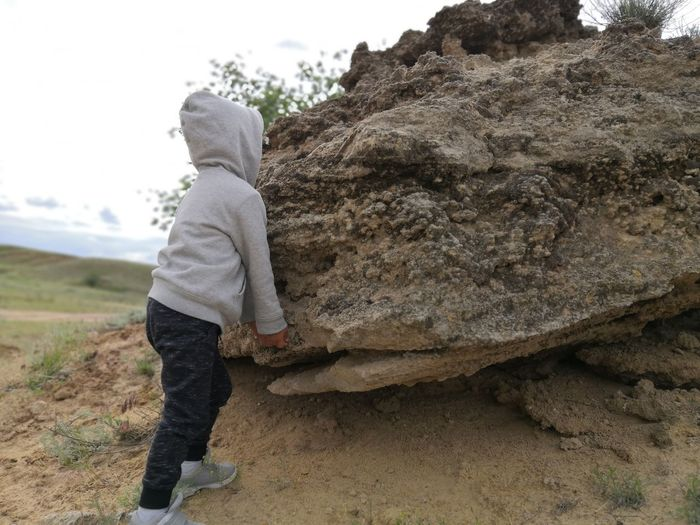 Side view of boy standing on rock