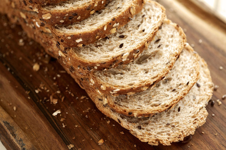 Sliced multigrain bread on cutting board. Diagonal view. Horizontal frame. Breakfast Diet Natural Wheat Bake Bakery Bread Brown Bread Close-up Crust Directly Above Food Food And Drink Grain Healthy Eating High Angle View Loaf Loaf Of Bread Multigrainbread No People Sliced Sliced Bread Studio Photography Wholegrain Wholemeal Bread