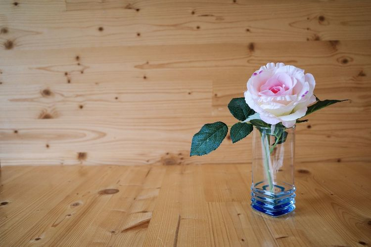 Close-up of rose in vase on wooden table