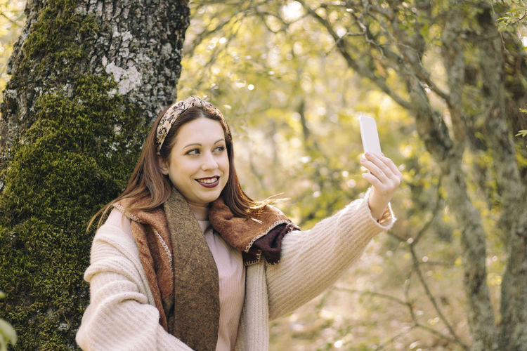Portrait of smiling young woman using mobile phone against trees