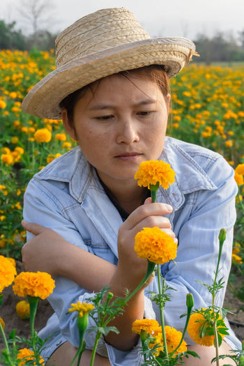 Marigold Portrait Flower Marigold Flower Farmer Selective Focus Lifestyles Outdoors Nature Plant Leisure Activity Care Check Hat Flowering Plant Real People One Person Front View Holding Child Clothing Growth Childhood Yellow Day Women Casual Clothing Sun Hat Gardening Flower Head