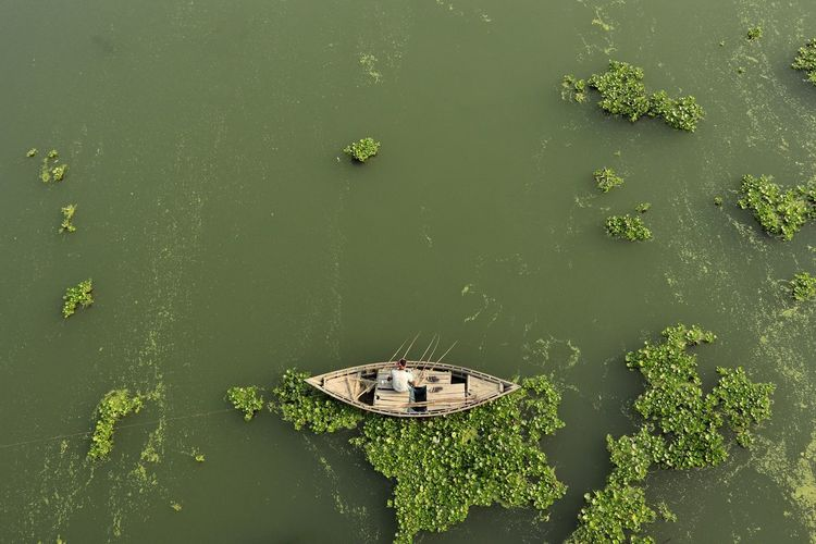 High angle view of boat floating on river and fishing by fishing rod